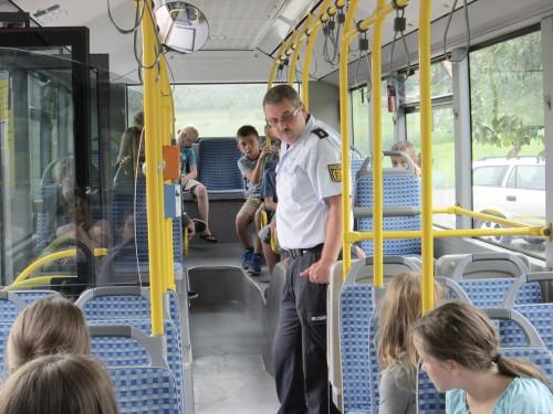 Polizeioberkommissar Herbert Erlenbusch erklärt den Schulkindern das richtige Verhalten im Schulbus. Foto: Strauss-Reisen